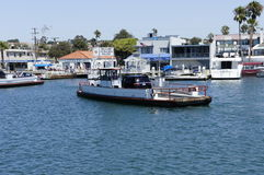 Welcome to Balboa Island. A barge is approaching the pier at the balboa island with several people are waiting at the pier Stock Photos