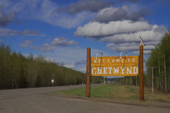 Welcome to Chetwynd. Welcome Sign to Chetwynd, British Columbia, Canada headed north on Highway 97 with blue cloud sky, trees and road stock photo