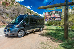 Welcome to Colorful Colorado State Road Sign near Utah/Colorado border going towards Norwood Colorado - with Winnebego Travado RV. Parked Stock Images