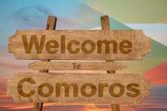 Welcome to Comoros sing on wood background with blending national flag Royalty Free Stock Images