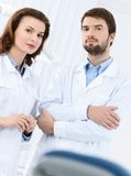 Welcome to the dental clinic. Dentist and his assistant welcome the patient to the dental clinic, white background Stock Photography