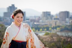 Welcome to Fukuoka, Japan. A beautiful young woman in graduation kimono with the city of Fukuoka, Japan, and Ohori Park in the background Royalty Free Stock Photography