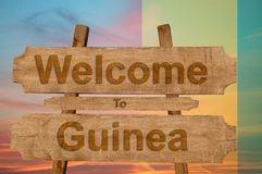 Welcome to Guinea sing on wood background with blending national flag Royalty Free Stock Image