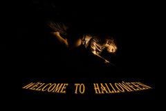 Welcome to Halloween. little girl with a broom on  black background  the words Stock Image