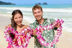 Welcome to Hawaii - Hawaiian people showing lei. S flower necklaces as a welcoming gesture for tourism. Travel holidays concept. Asian women and Caucasian men on Royalty Free Stock Image