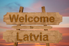 Welcome to Latvia sign on wood background with blending national flag Stock Photography