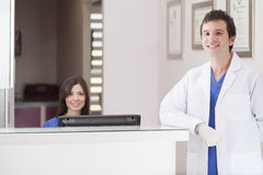 Welcome to my dental office. Male dentist and assistant greeting patients at the front desk Royalty Free Stock Images
