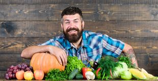 Welcome to my farm. Man bearded farmer harvest wooden background. Farmer with homegrown vegetables. Vegetables organic. Harvest. Farmer rustic style guy stock photography