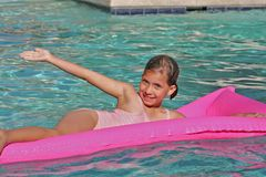 Welcome to my fun. Girl on a pink pool raft Royalty Free Stock Images