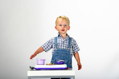Welcome to my kitchen. Cute blond toddler boy cooking in his toy kitchen making an inviting gesture Stock Images