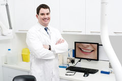Welcome to my modern dental office. Happy dentist posing with computer screen Royalty Free Stock Images