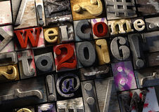 Welcome to 2016 New Year title in vintage colorful wood block te. Xt. Social media hashtag with grunge concrete background. Rough wooden blocks celebration of Stock Image