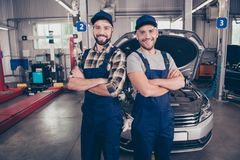 Welcome to our car service. Two experts with arms crossed, smil. Ing at camera, in special safety outfit and glasses, headwear, standing over background of Stock Photos