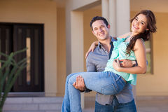 Welcome to our new home. Happy newlyweds arriving to their new home and smiling Stock Image