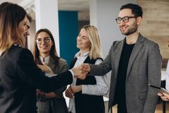Welcome to our team! Top view of young modern men in smart casual wear shaking hands while working in the creative office royalty free stock photo