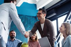Welcome to our team! Young modern men in smart casual wear shaking hands while working in the creative office. stock image