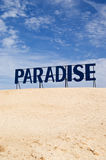 Welcome to Paradise. Paradise guide board between desert sand and blue sky Royalty Free Stock Images