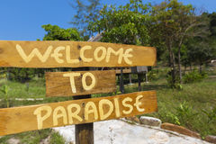 Welcome to paradise sign with green trees and blue sky in Cambod Stock Photos