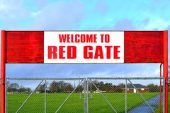 Welcome to Red Gate Sign. An old textured red wooden sign indicating Welcome to Red Gate, above a gray (grey) metal gate. There may be conceptual irony, in that Royalty Free Stock Image
