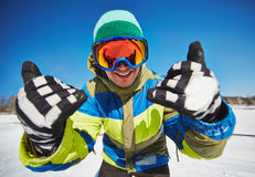 Welcome to resort. Young snowboarder in sportswear looking through protective eyeglasses at winter resort Stock Photography