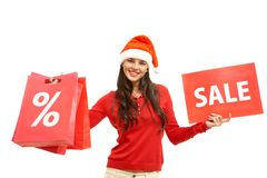 Welcome to sale. Happy girl in Santa cap holds card and paperbags with symbols of sale Royalty Free Stock Image