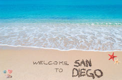 Welcome to San Diego. Turquoise water and golden sand with shells and sea stars with welcome to san diego written on it Stock Photos