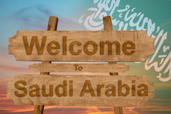 Welcome to Saudi Arabia sign on wood background with blending national flag Royalty Free Stock Photography