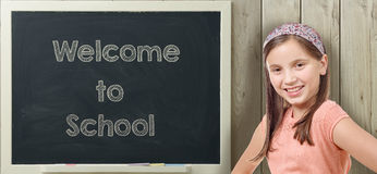 Welcome to school written on  blackboard with young girl. Welcome to school written on  blackboard with pretty young girl Royalty Free Stock Images