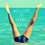 Welcome to spring break. The text welcome to spring break written on a blurred image of a young man upside down into the sea stock image