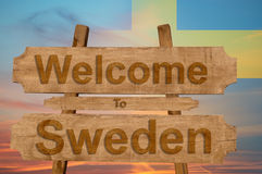 Welcome to Sweden sign on wood background with blending national flag Royalty Free Stock Photo