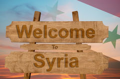 Welcome to Syria sign on wood background with blending national flag Stock Photos