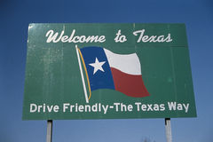 Welcome to Texas sign. This is a road sign that says, Welcome to Texas, drive friendly, the Texas way. It is against a blue sky with he Texas state flag in the stock photo