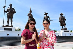 Welcome to thailand. Portrait beauty twin Thai girl with giant Kings statues and blue sky in action welcome, Rajabhakti Park Thailand Stock Photography