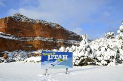 Welcome to Utah. Utah welcome sign with cliffs and snow covered trees Stock Photo