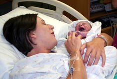 Welcome to the World. A mother holds her newborn infant before the nurses take him away to his first bath Stock Photos