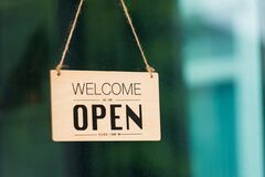 Free WELCOME WE ARE OPEN PLEASE COME IN Notice Sign Wood Board Label Hanging Through Glass Door Royalty Free Stock Photo - 194492485