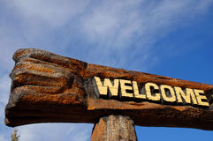 Welcome. Wooden welcome sign with bright blue sky and white clouds in background stock photography