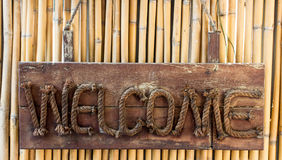 Welcome wooden sign hanging on a rope on bamboo b Royalty Free Stock Photography