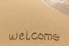 Welcome - word drawn on the sand beach Stock Photos