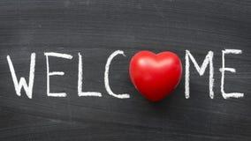 Welcome. Word handwritten on blackboard with heart symbol instead O Stock Photos