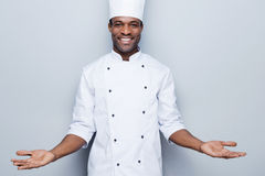 Welcome in the world of tastes. Confident young African chef in white uniform keeping arms outstretched and smiling while standing against grey background Royalty Free Stock Photography