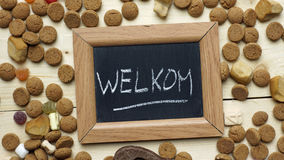 Welcome writren in Dutch. Welcome in Dutch written on a chalkboard between ginger nuts and candy's for the Dutch Santa-Claus celebration of the 5th of December Royalty Free Stock Image