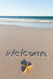 Welcome written on a beach. Australia. Welcome written on a sandy beach. Starfish in the foreground. Australia Royalty Free Stock Photos