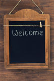 Welcome written with chalk on aged blackboard hanging on wooden wall Stock Photo