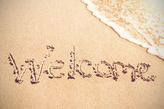 Welcome written on sand Stock Photos