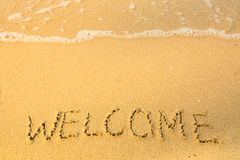 Welcome, written in sand on beach texture, soft wave of the sea. Travel. Stock Photos
