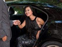 Welcomed. Gallant man offering his hand to a glamorous lady in the car Stock Image