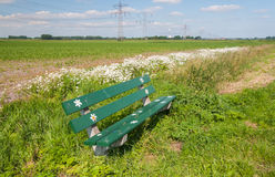 Welcoming bench in an agricultural landscape. Green bench with flower stickers on the edge of an arable field Royalty Free Stock Images