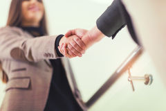 Welcoming business woman giving a handshake. And smiling royalty free stock image