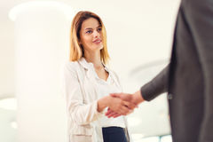 Welcoming business woman giving a handshake Stock Images